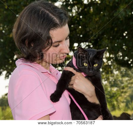 Young woman holding a black cat in harness in her arms