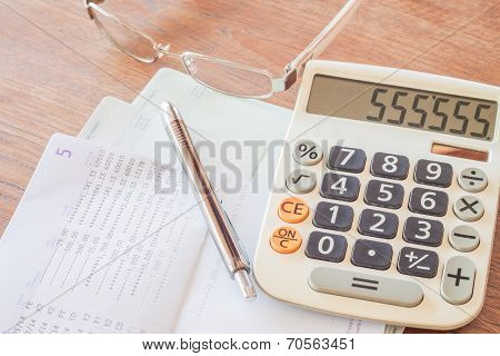 Calculator, Pen And Eyeglasses On Bank Account Passbook