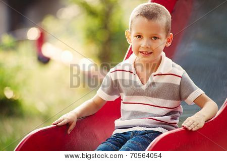 Small Boy Playing On A Slide In A Kids Playground