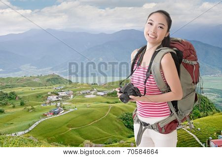 Happy smiling Asian young female backpacker with camera standing in front of tiger lily farm in Liushidan mountain, Fuli Township, Hualien County, Taiwan, Asia.