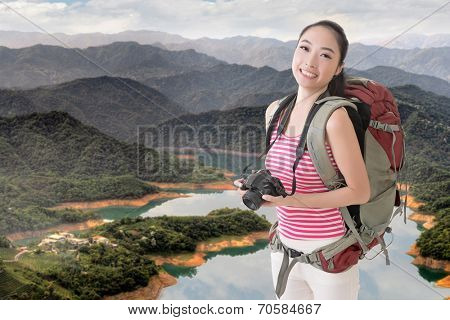 Happy smiling Asian young female backpacker with camera in the countryside.