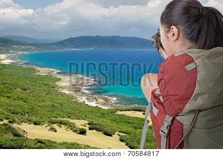 Asian female backpacker take photo in front of beach of Kenting, Taiwan, Asia.