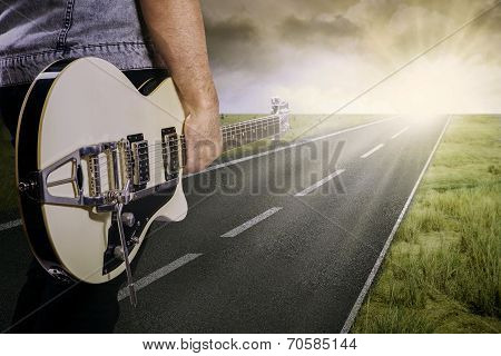Guitarist And His Guitar On The Road