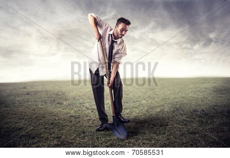 businessman digging in a field