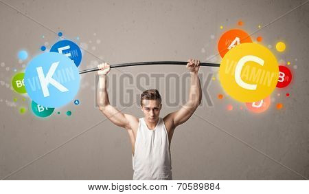 Strong muscular man lifting colorful vitamin weights