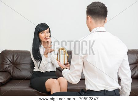 Young businessman giving a flower to pretty colleague and standi