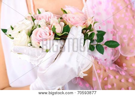 Beautiful bride in white gloves holding wedding bouquet, close-up
