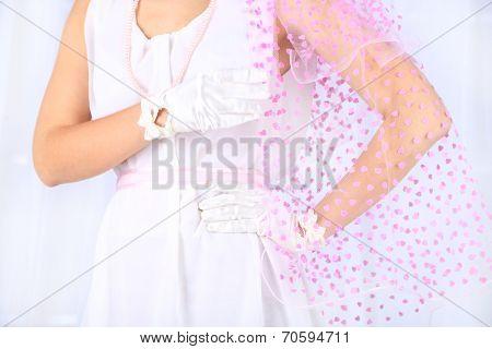 Beautiful bride in wedding  dress and gloves, close-up, on light background