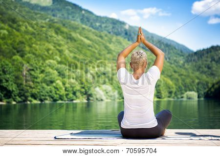 young woman practicing yoga meditation front lake