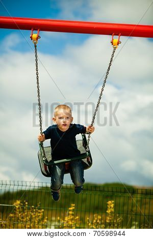 Little blonde boy having fun at the playground.
