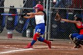 picture of fastpitch  - young lady fastpitch softball player reaches with glove to catch the ball but the batter makes contact and hits the ball. 