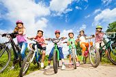 stock photo of bike path  - Below angle view of kids in helmets who hold their bikes and stand on path - JPG