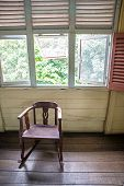 stock photo of guayaquil  - Isolated old rocking chair under several windows in a 19th century model house - JPG