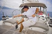 stock photo of sail-boats  - Man sailing a sailboat pulling the ropes tight - JPG