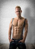 picture of nearly nude  - Sexy portrait of a very muscular blond shirtless male model smiling near brick wall - JPG