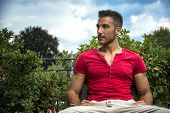 pic of sitting a bench  - Good looking fit male model relaxing sitting on bench outdoors looking to a side - JPG