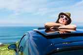stock photo of recreational vehicles  - Relaxed day dreaming woman on summer travel vacation leaning out car sunroof towards the sea - JPG