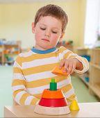 stock photo of montessori school  - boy collects colored pyramid school Maria Montessori - JPG
