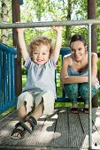 stock photo of mums  - Happy mum and son on the playground - JPG