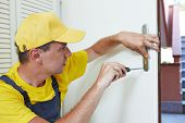 stock photo of handyman  - Male handyman carpenter worker at interior wood door lock installation or repairing - JPG