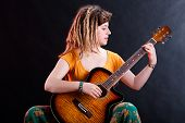 pic of dreadlocks  - Young girl with dreadlocks playing acoustic guitar - JPG