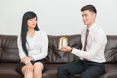picture of office romance  - Side view of Business couple in formal clothing sitting on sofa in office - JPG