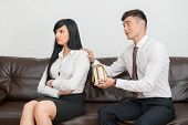 foto of begging  - Side view of Business couple in formal clothing sitting on sofa in office - JPG