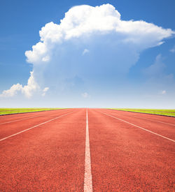 foto of olympiade  - red running track over blue sky and clouds - JPG