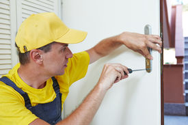 picture of handyman  - Male handyman carpenter worker at interior wood door lock installation or repairing - JPG