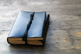 foto of leather-bound  - A leather bound journal sits on a table outside with a cord wrapped around the pages to keep place in book - JPG
