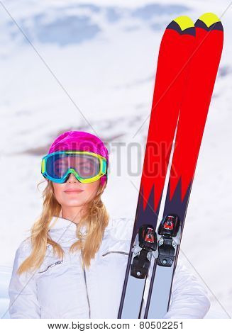 Portrait of sportive woman wearing cute pink hat and goggles holding in hands red ski, enjoying extreme winter sport, travel and vacation concept