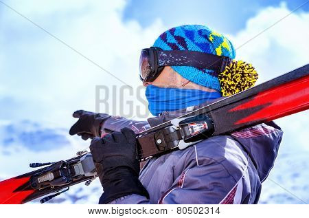 Ski trainer standing on the top of mountain and showing direction, extreme winter sport, holding in hands sports equipment, active wintertime holidays concept