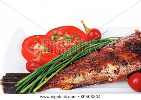 savory isolated on white: whole fried sunfish over plate with tomatoes lemons and peppers