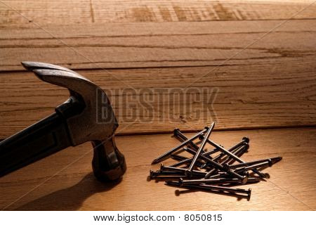 Pile Of Nails And Claw Hammer On Wood Boards