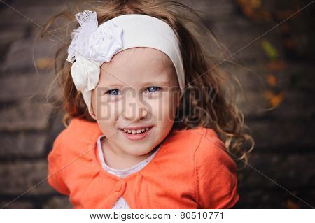 beautiful smiling child girl portrait with stone road on background