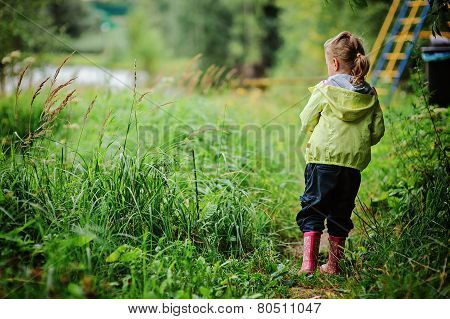 little girl in rubber boots and yellow jacket on the walk on summer river side