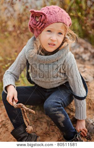 vertical autumn portrait of adorable child girl in pink knitted hat on sand river side