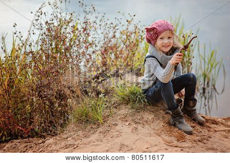 adorable happy child girl in pink knitted hat plays with stick on river side