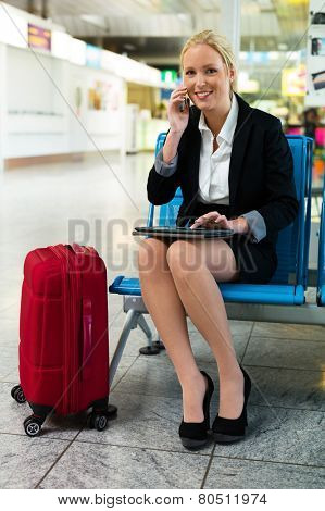 a businesswoman using her phone and a tablet computer at an airport. mobility and communication in business. roaming charges when abroad.