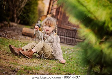 adorable happy child girl with pigtails having fun in spring garden