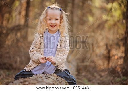 adorable smiling blonde child girl in blue shirt on the walk in early spring forest