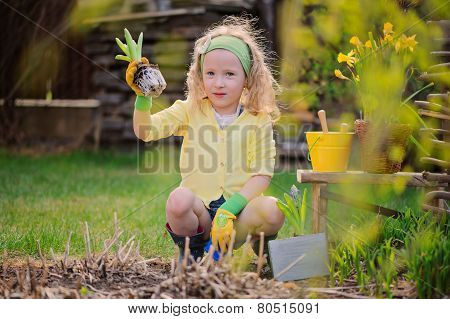 beauty child girl plays little gardener and planting flowers in spring garden