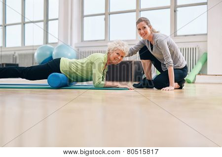 Gym Coach Helping Elderly Woman In Her Workout