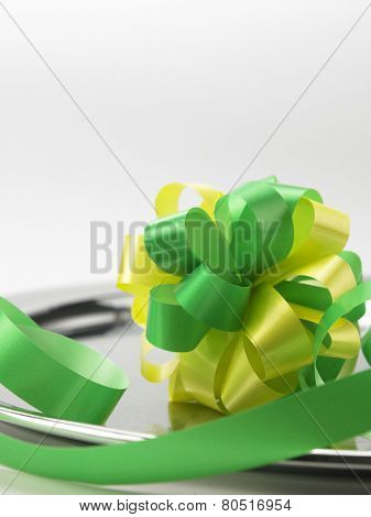 green yellow ribbon bowl on the silver plate