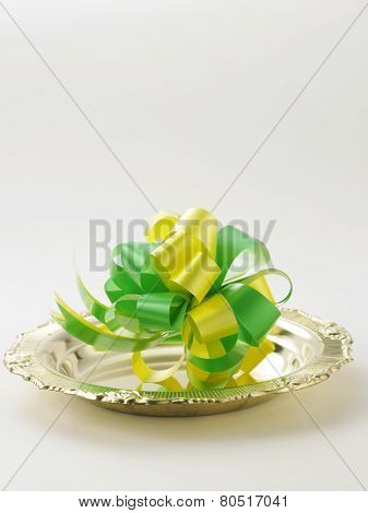opening ceremony concept,green bows on the golden plate