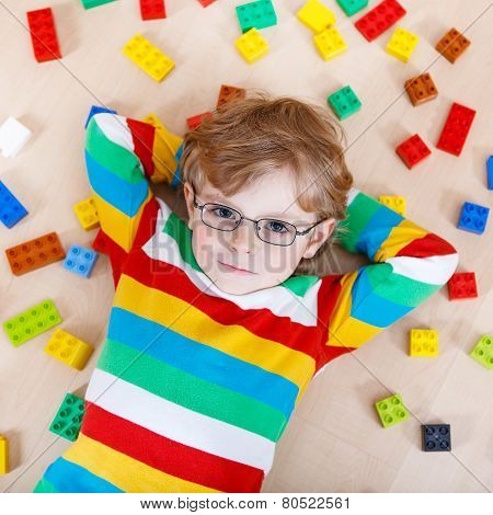 Little Blond Kid Boy Playing With Lots Of Colorful Plastic Blocks Indoor