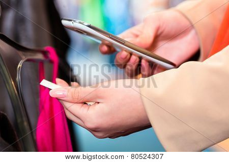 Woman shopping in boutique or fashion store comparing prices with mobile phone scanning the price tag