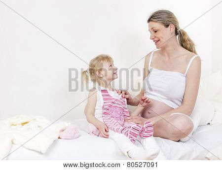 little girl and her pregnant mother with clothes for a baby
