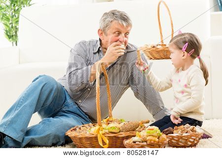 Grandfather And Granddaughter Eat Pastry
