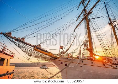 Old sailing ship in the rays of light of the setting sun in the port